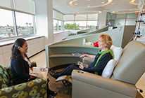 A patient talks with a guest during treatment at UCI Health Cancer Center — Newport's new infusion center.