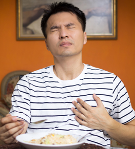 man eating and having heartburn