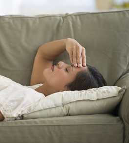 woman sick with the flu lying down on couch