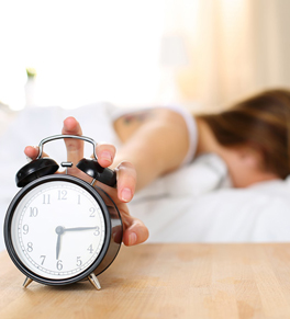 woman hitting snooze on alarm clock