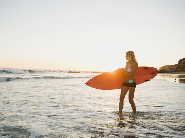 woman with surfboard getting vitamin d from sun