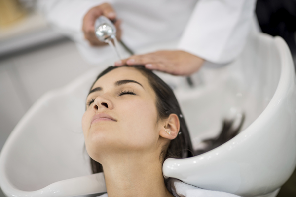 woman getting hair shampooed at salon
