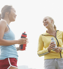 women exercising and drinking water to stay hydrated