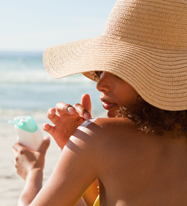 woman wearing hat putting on sunscreen