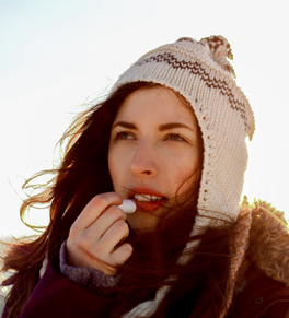 woman moisturizing lips in cold weather