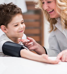 doctor taking young boy's blood pressure