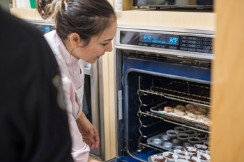 woman removing food from oven