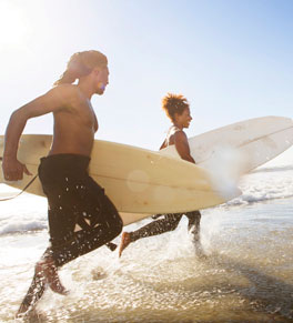 teens running into water with surfboards