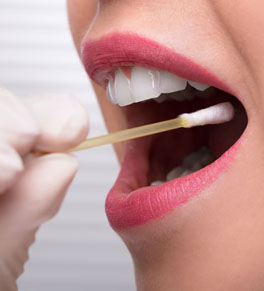 woman swabbing mouth for home genetic test