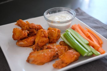 baked chicken wings in hot sauce with carrots and celery
