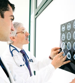 doctors examining patient brain scan for aneurysm