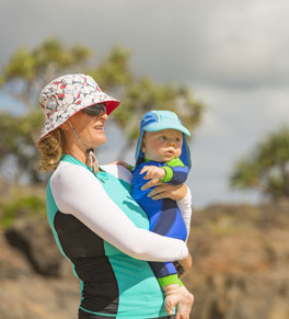 woman and baby on the beach wearing sun protection