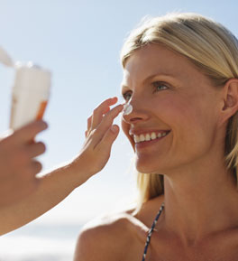 woman having sunscreen applied to face