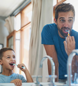 father and son brushing teeth together in bathroom