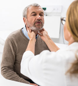 man being examined by doctor for throat cancer
