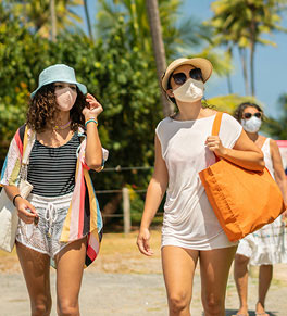 Young women stroll near the beach wearing masks to protect against COVID-19.