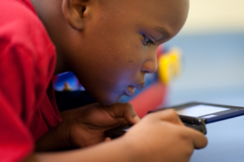 Akintunde Udo, 6, is engrossed in a game at a UCI Health center for patients with autism.