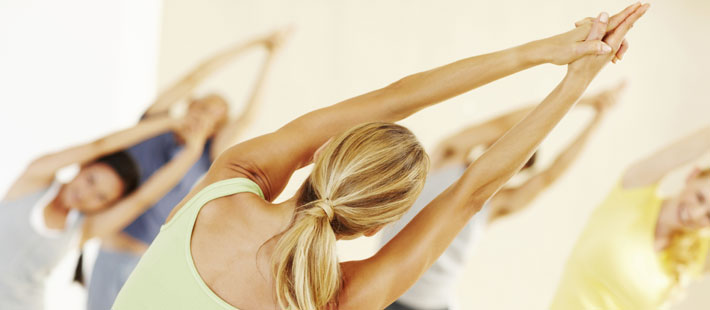 women stretching spine in exercise class