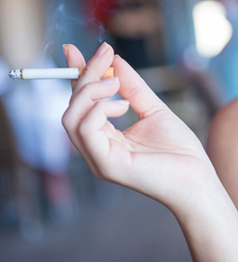 woman's hand holding lit cigarette