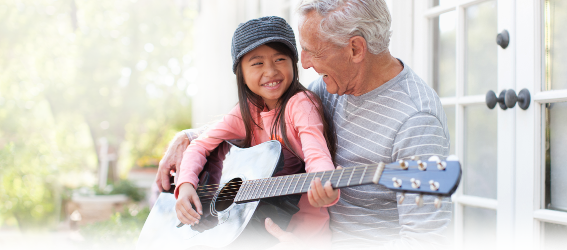 man playing guitar with granddaughter