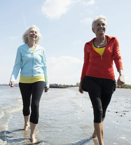 two women walking on beach smiling