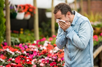 man sneezing in a flower shop