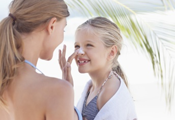 woman applying sunscreen to child's nose