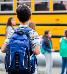 boy waiting to board school bus with backpack