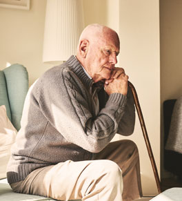 older man with cane in pain