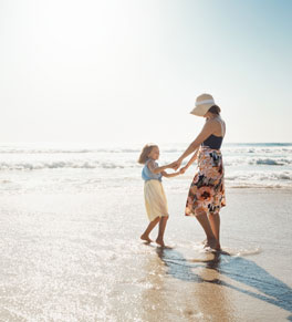 woman and child playing on beach