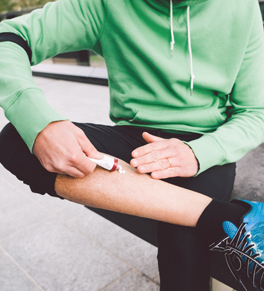 man putting cbd cream on leg after run