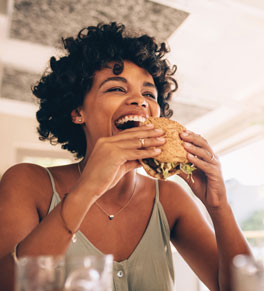 woman eating burger after intermittent fasting