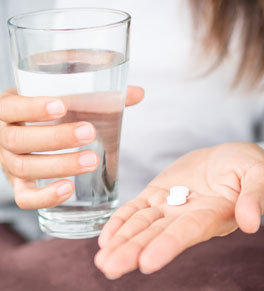 woman taking aspirin with a glass of water