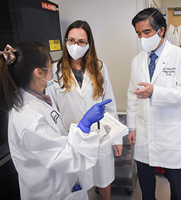 Lab scientist Sidney Huang, left, consults with microbiology lab director Dr. Cassiana Bittencourt, center, and Dr. Edwin S. Monuki, head of UCI Health Pathology & Laboratory Services.
