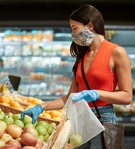 Masked woman shops for fruit and vegetables