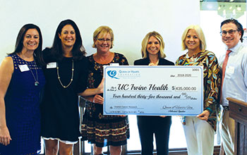 Members of the Queen of Hearts Foundation present donation check to Dr. Leslie Randall of the UCI Health gynecologic oncology team.