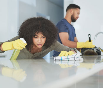 couple disinfecting their home with gloves