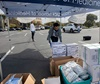 UCI medical student Mehron Dhillon stacks donations of personal protective equipment during a drive for supplies in the UCI School of Medicine parking lot.