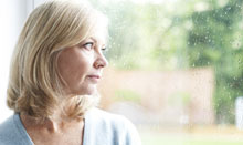 woman with seasonal affective disorder looking out window